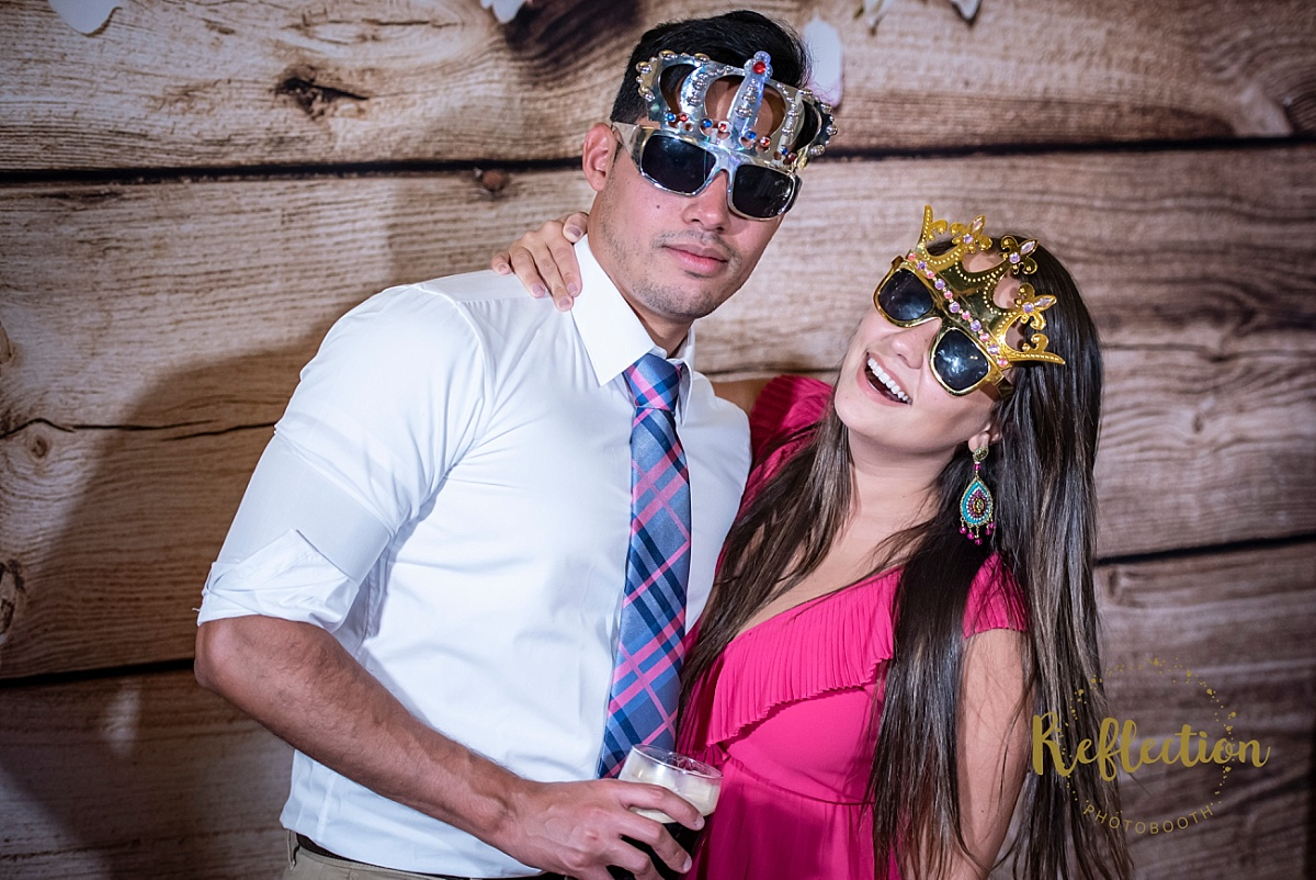 Flagstaff Photo Booth at a wedding in a barn with log walls with the subjects wearing silly glasses and crowns