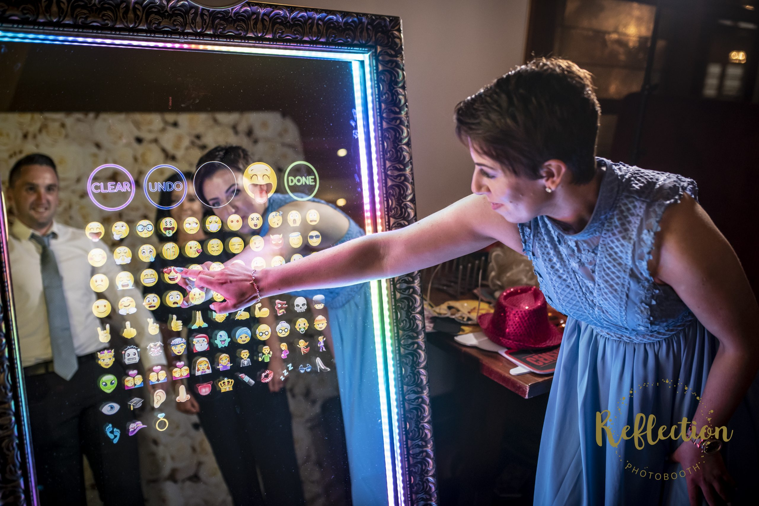 Mirror Photo Booth with guest signing the booth photos with emojis